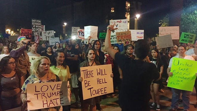 Organizer Randy Perez talks to protesters with a megaphone on Nov 12, 2016 in Tempe, Ariz.