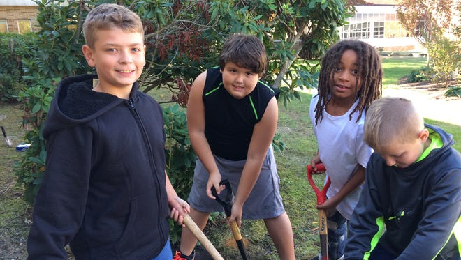 (From left) Liam Harvey, Addison Finckbone, Myshawn Parker and Chet Tostevin, students in Kim Jackson's class at Rieck Avenue School in Millville, plant daffodil and tulip bulbs in the courtyard in memory of their beloved classmate Melissa Headley.