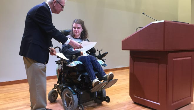 Writers Harvest organizer Mike Pulley held up pages for Miriam McEwen to read from her story Harebrained Youth at Thursday's event. McEwen, a Mountain Rest native, suffers from Cerebral Palsy.