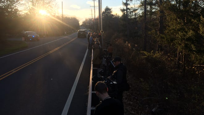 Reporters gather along Lamington Road near the entrance of Trump National Golf Club in Bedminster as dusk descends Friday evening.