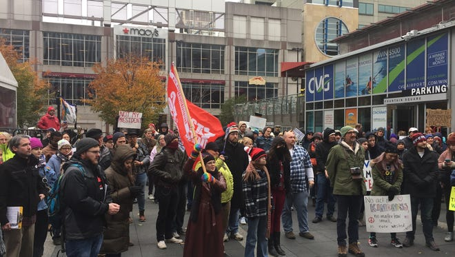 More than 100 people bundled up and gathered on Fountain Square Saturday afternoon to protest against President-elect Donald Trump.