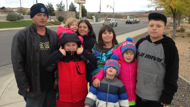 A homeless family stands on the corner near Costco in Washington City asking for donations Sunday, Nov. 20, 2016. The family said they collect the money to rent a motel room for a night to get by.