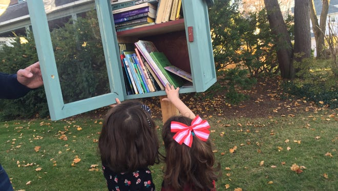 Caroline and Felicity Clarke check out the books in the Little Free Library.