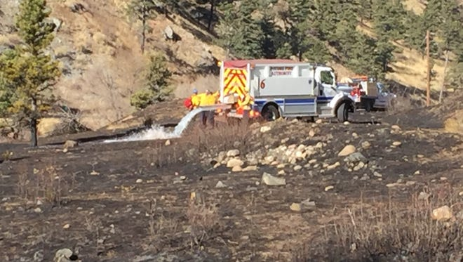 Poudre Fire Authority crews mop up after a small brush fire in Poudre Canyon on Thursday.