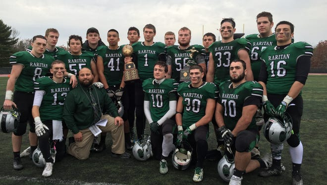 Raritan football seniors pose with head coach Anthony Petruzzi and the border trophy.
