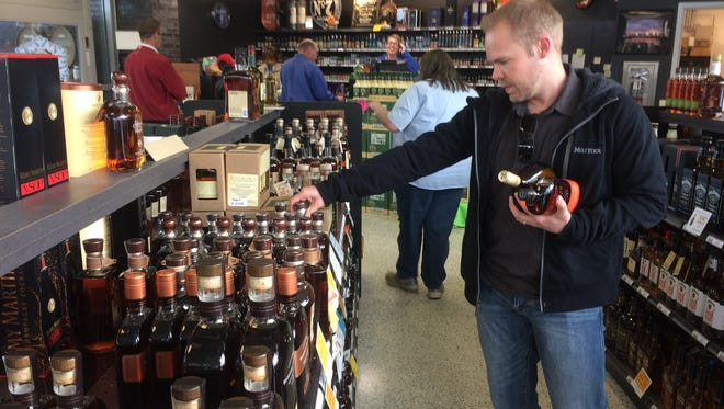Liquor sales are up system-wide for the Asheville ABC Board, in part driven by younger consumers like Jon Abbotts, here shopping for high-end bourbon at the Hendersonville Road ABC store.