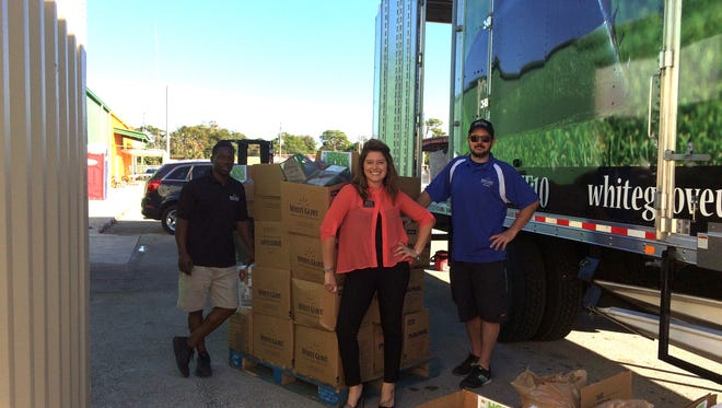 Rickie Stinson, Anna Valencia Tillery and Archie Edwards of White Glove Moving & Storage gather more than 2,500 pounds of donated food during the company's holiday drive.