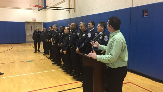 Kyle Crandall, right, president of the Beechwood Neighborhood Coalition, honors Rochester police officers and firefighters during the association's annual dinner Thursday at the Thomas Ryan Community Center.
