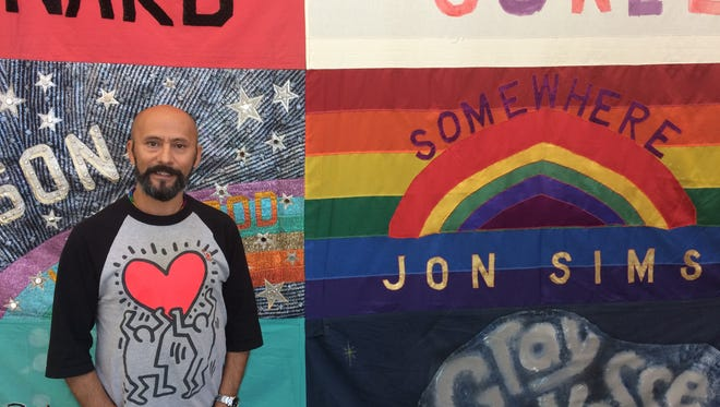 Event organizer Kelly Rivera Hart stands in front of panels from the AIDS Memorial Quilt on display at The Bank in Palm Springs on Dec. 2, 2016.
