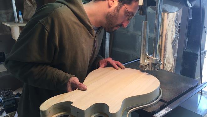 Steve Flicker of Kingston at work building a guitar.