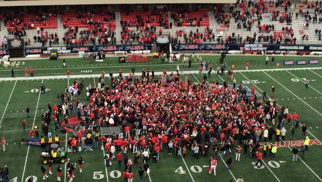 WKU players, coaches and fans rush the field after the Hilltoppers 58-44 win over Louisiana Tech to capture their second-straight Conference USA title.