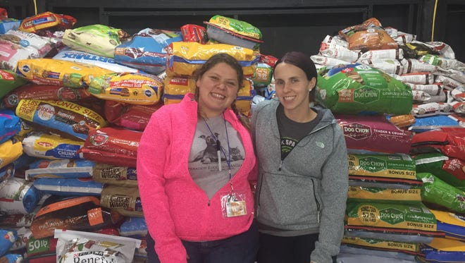 Tiffany Galyon with Operation Education Animal Rescue stands with JJ Blevins in front of a pile of supplies.