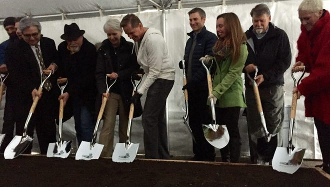 A row of local leaders, including Marc Moen, center, use shovels to break ground at the future site of the Chauncey Tower on Dec. 11, 2016.