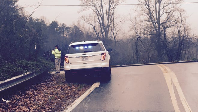 A Buncombe County sheriff's detective photographs the scene where a jogger was attacked early Monday morning.
