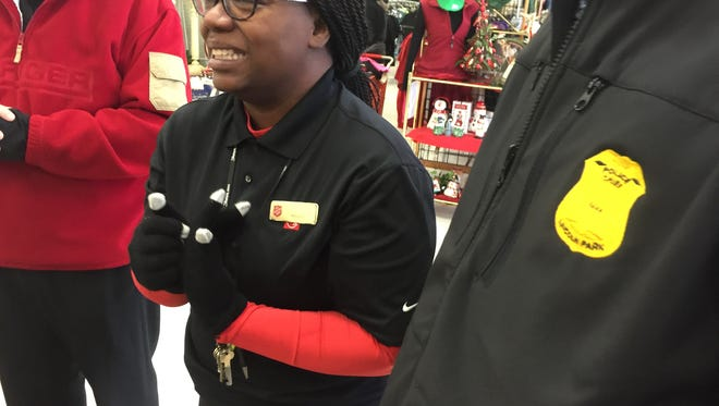 Denisha Hoover of River Rouge, manager of a Salvation Army thrift store in Lincoln Park, cries after Secret Santas gave her and other employees gifts of $100 bills on Monday, Dec. 12, 2016.