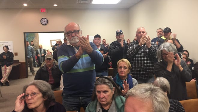 Bernardo Licata, other residents and members of the Clay Township fire department stand up in applause during public comment.