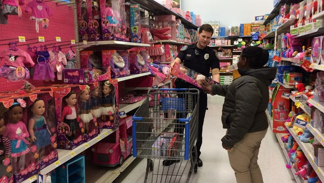 """Nine-year-old Zamaria Johnson picking out a Barbie doll during """"shop with a cop."""""""