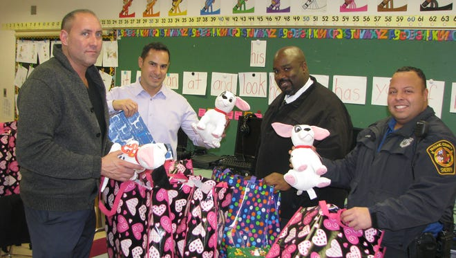 Passaic County sheriff's officers stuffing bags of toys at School 1 on Thursday. From left, John Welsh, Ricky Rosario, Robert Scott and Carlos Alejo.