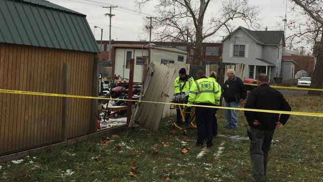 Delaware County emergency medical personnel prepare to remove a body found Thursday morning in a storage shed in the 1200 block of East Kirby Avenue.