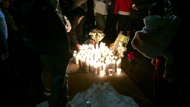 Many people lit candles and said prayers at the site in Chandler where Dominic Vega, 20, was killed by an unknown gunman Wednesday night.