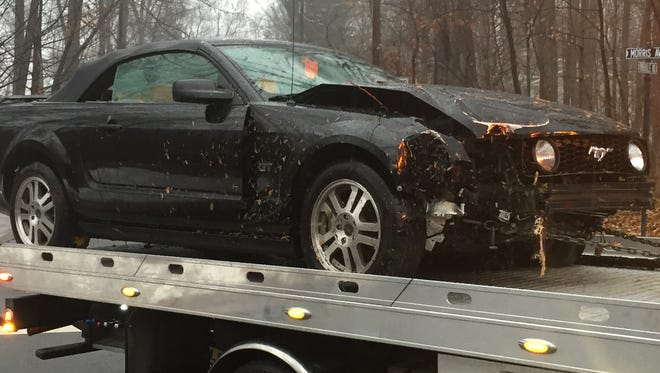 A Ford Mustang that overturned early Christmas Eve morning on Morris Avenue in Mountain Lakes is carted away from the scene.