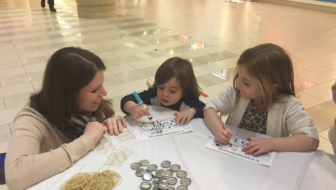 Shari Spinale of Wappingers Falls look on as her children, William, 2, and Sophia, 4, use markers to color a drawing of Jerusalem during a Hanukkah celebration at the Poughkeepsie Galleria Monday.