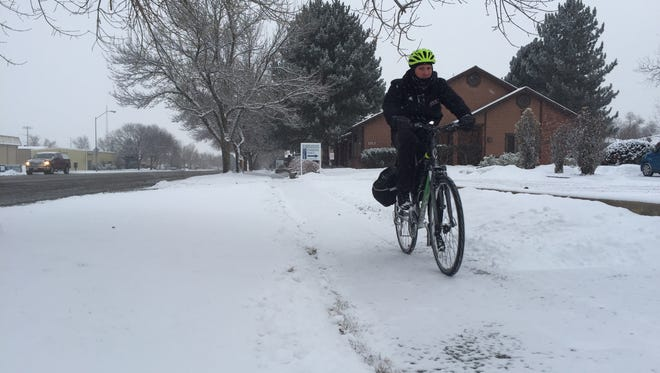 A biker rides on Riverside Avenue in Fort Collins on Tuesday, after about 2 inches of snow fell in the area.
