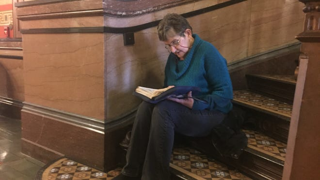Jo Ann Kruckvich of Centerville reads aloud from her Bible Tuesday, Jan. 3, 2017, on a staircase in the Iowa Capitol.