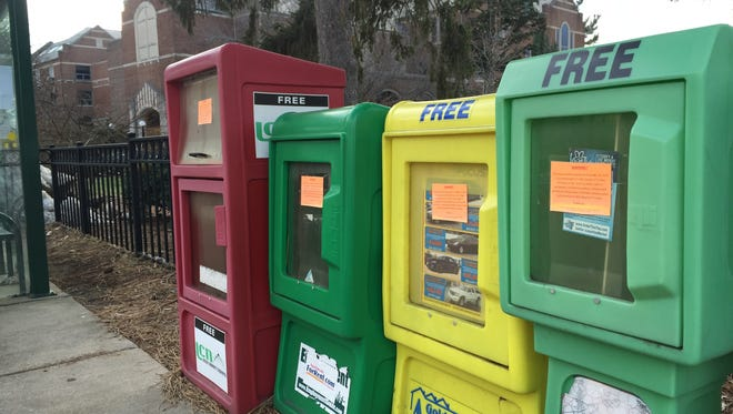 A slew of newspaper kiosks at the corner of Grand River and Abbot in East Lansing bare orange warnings of impending removal by staff at Michigan State University Thursday, Dec. 29, 2016.