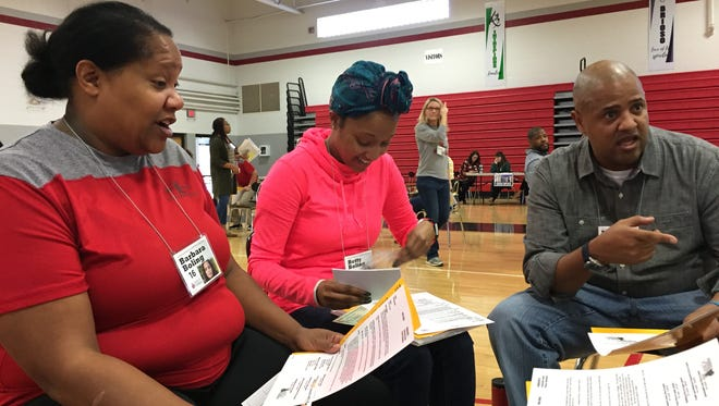 Discussing their characters during a poverty simulation are, from left, Latoria McKenzie, Britney Christon and Cary Holman. Later during the simulation, the group was evicted from their 'home.'