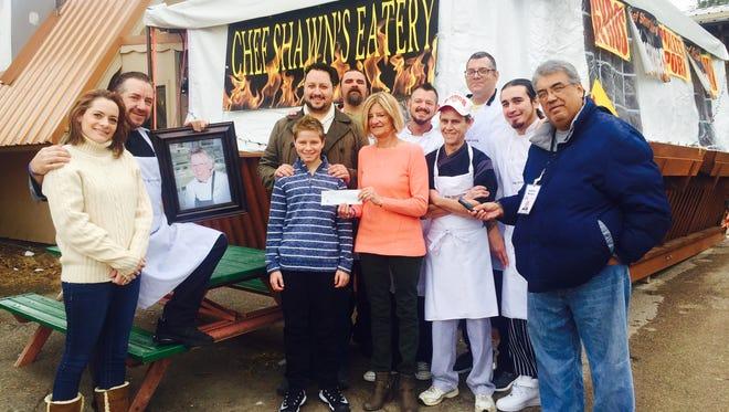 Doris Schoffthaler and members of White Apron Society present a $7,000 check to Ethan Glass to support his sister, Ella Glass, during her cancer treatments in Denver, Colo.