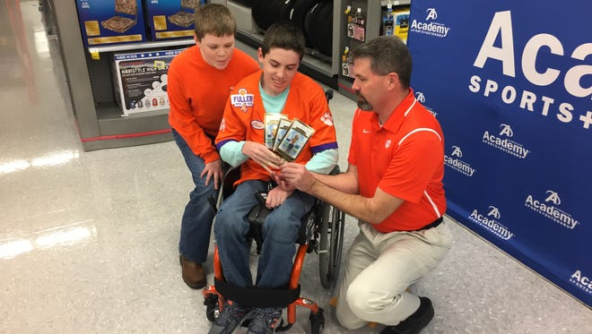 Carson, Logan and Bill Wires check out their tickets for Monday's national championship games at Academy Sports + Outdoors in Anderson. The store gave the family the tickets.