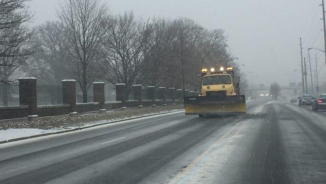 A plow rolls down 38th Street near Crown Hill Cemetery on Thursday.