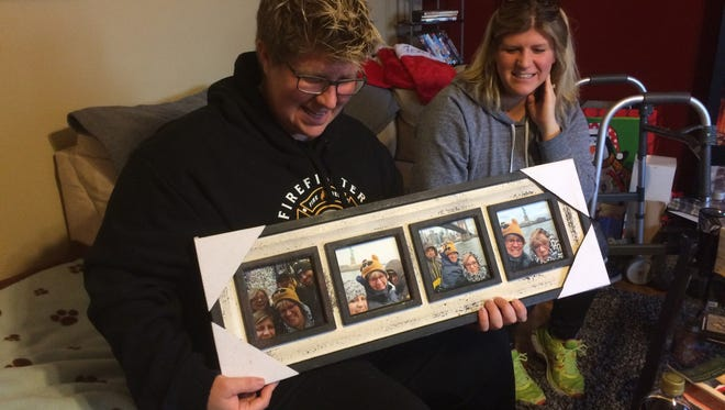 Beth Csukas shows off photos of her during a recent New York City trip while sister Brooke Csukas Raisor looks on. For Christmas, Csukas gave her family members similar collections of photographs so her face could be on all of their walls. Csukas, an Evansville firefighter, was injured in a vehicle crash last January