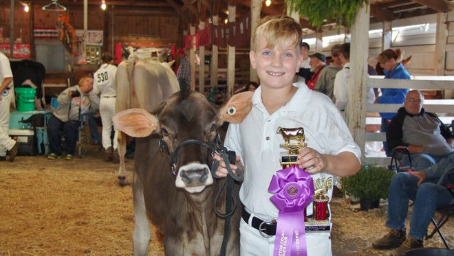 Grant Lahmers poses with one of his Brown Swiss heifers during the dairy show at the Coshocton County Fair. The program – which is open to youth from all dairy breeds as long as they reside in Wisconsin – aims to help young people interested in working with dairy cattle gain hands-on experience with high quality registered Brown Swiss.