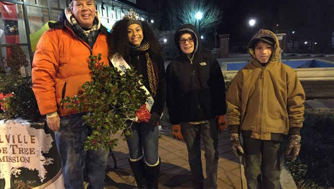 Daleishka Torres, Miss Holly City 2016, along with members of Boy Scout Troop 37, distributed holly for the Millville Shade Tree Commission outside of the Riverfront Renaissance Center for the Arts on Dec. 16.