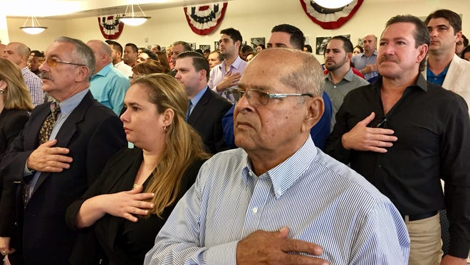 "Alberto Vilches (center) prepares to take the oath of allegiance to become a U.S. citizen at U.S. Citizenship and Immigration Services office in Miami on Jan. 13, 2017. The Havana native benefited from the ""wet foot, dry foot"" policy."