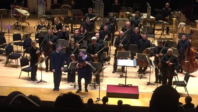Violinist Pekka Kuusisto takes bows with conductor Matthias Pintscher and the CSO