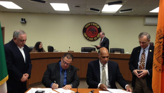 """Far left, Leonardo Marzullo, president of Club Aquilonese San Vito Martire, based out of Our Lady of Mount Carmel Church, and At-Large Township Councilmember Bob Russo, far right, watch as Raffaele Marzullo, left, and Mayor Robert Jackson sign an agreement to become """"Sister Cities"""" with Aquilonia, Italy, on Jan. 24, 2017."""