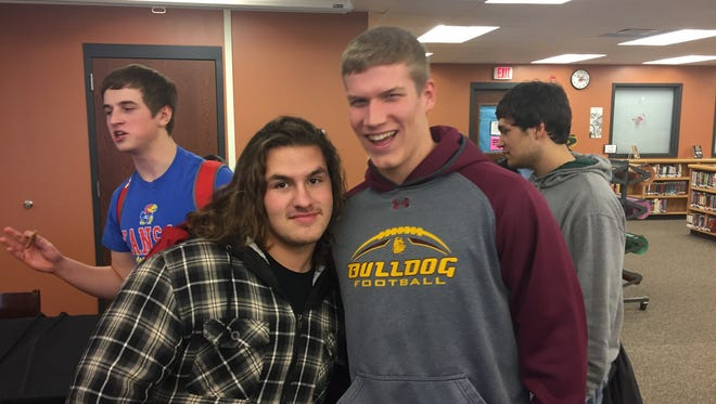 Teammate Mitchell Kunkel gets himself into a photo with Rocori football teammate Nathan Thorpe on Wednesday at Rocori High School. Thorpe signed an NCAA national letter of intent to play football at Minnesota-Duluth.