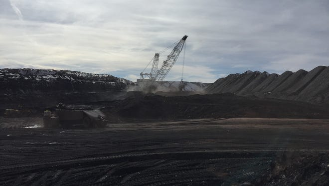 A dragline dumps a load of coal as a truck descends the ramp into the Kayenta Mine pit on Feb. 2, 2017.
