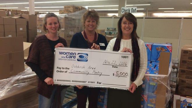 Terri Green, executive director of the Oshkosh Area Community Pantry receives a donation from representatives of Women Who Care Greater Oshkosh, Heidi Reinke and Wendy Potratz.