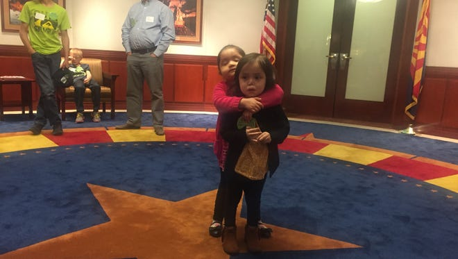 Three-year-old Joy Littlesunday gives a big hug to her friend Ava George, also 3, at the state Capitol. Both girls were born with severe combined immunodeficiency, or SCID, which Gov. Doug Ducey wants to include in screening tests required for Arizona newborns.