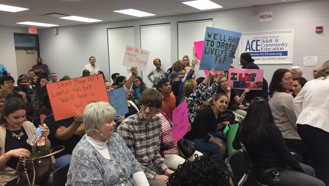 Students, parents and teachers from ACE hold signs in favor of staying in their Trojan Trail campus at a Feb. 8 meeting.