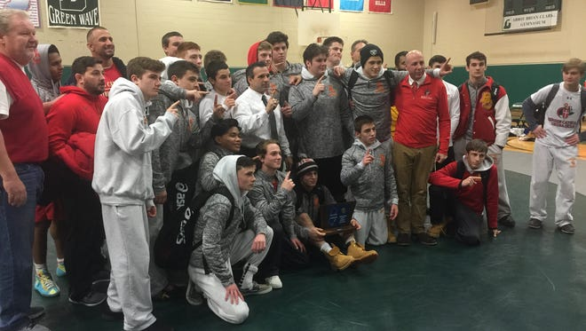 Members of the Bergen Catholic wrestling team pose with their sectional title trophy after beating Delbarton, 28-23.