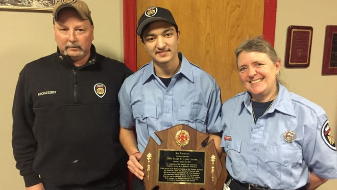 Bala Chauwan, 20, center, was honored as the Harry B. Austin Protective of the Year Friday night. Rochester Fire Protectives Chief Mark Kirchgessner, left, and Laurie Kingsley-Henry, treasurer of the Protectives, delivered the news.