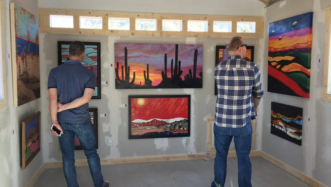 Visitors view works by Cathedral City artist Gene Poe in his newly built studio.