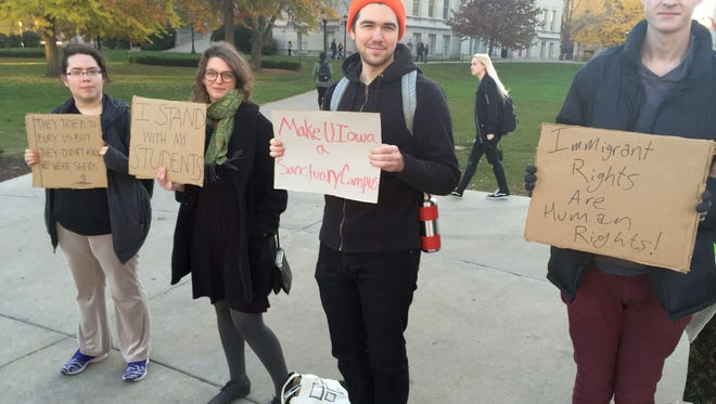"""In this file photo, students rally in November 2016 outside the Old Capitol on the University of Iowa campus. The Iowa State University Student Government Senate is debating Wednesday whether to ask university administration to have the Ames-based university declared a """"sanctuary campus."""""""