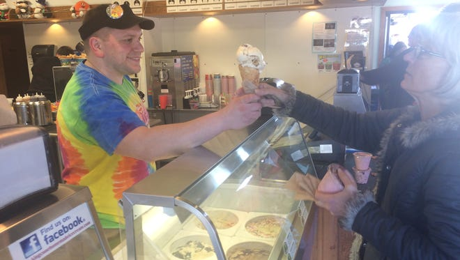 Ben Klosinski, manager for King Cone in Plover, hands out some ice cream on opening day for the business on Feb. 17, 2017.
