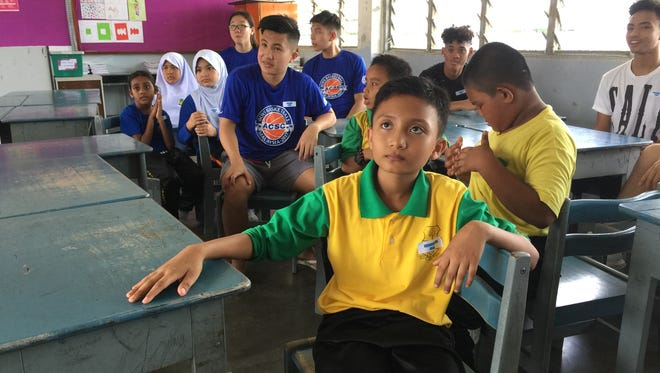St. Paul Christian Warriors' players at an English immersion lesson with students from an elementary school in Penang, Malaysia.